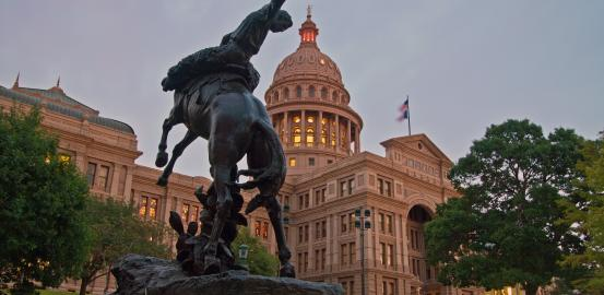 Texas state capitol with cowboy statue in front of building