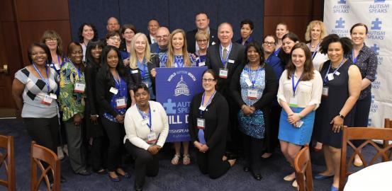 Group of Advocacy Ambassadors posing for photo with Hill Day poster