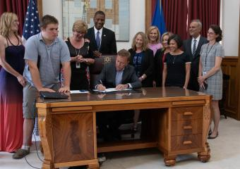 Governor Lamont signing bill and surrounded by advocates