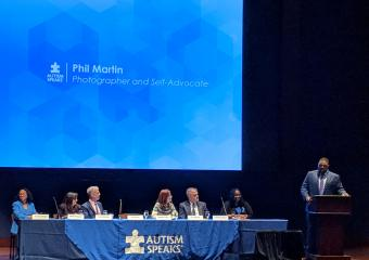 Phil Martin presenting at podium with panelists sitting at long table