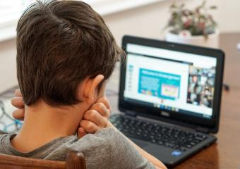 boy looking at laptop screen that shows a video conference presentation