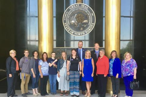 Group of advocates standing below the North Dakota State Seal