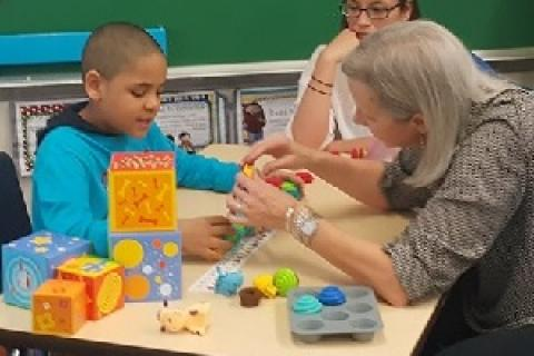 A mom works with a child who has autism during a Caregiver Skills Training workshop. Photo courtesy Mom2Mom