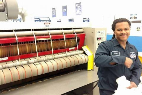 A Cintas employee with autism operates the napkin press.