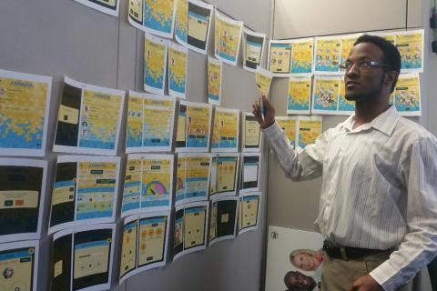 A young African American man organizes his thoughts using screenshots on a bulletin board.