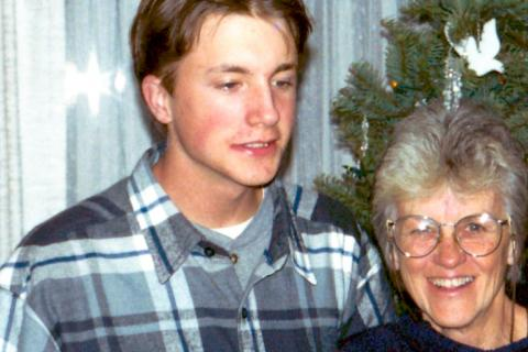 A picture of a young man in a plaid shirt and his mother in a navy shirt in front of a Christmas tree, smiling.