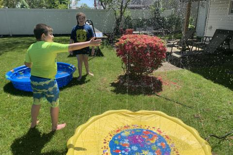 James Guttman's children playing in a sprinkler.