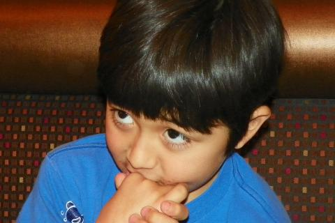 Young boy in blue shirt with hands clasped.