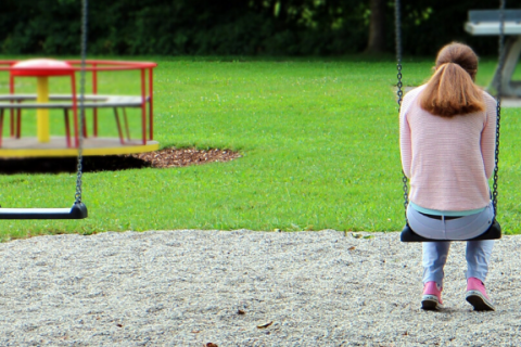 Girl sitting on a swing set alone in a park