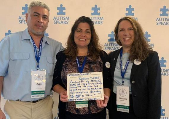 Advocates Juan Dipini, Claire Malfaro and Christine Ramsay standing in front of an Autism Speaks banner