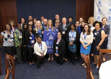 Group of 25+ Advocacy Ambassadors standing with World Autism Month Hill Day sign