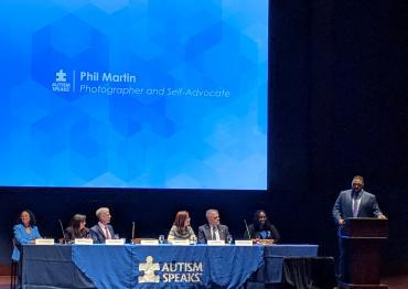 Фил Мартин выступает на трибуне с участниками дискуссии за длинным столом