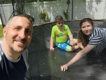 James Guttman with his kids on the trampoline