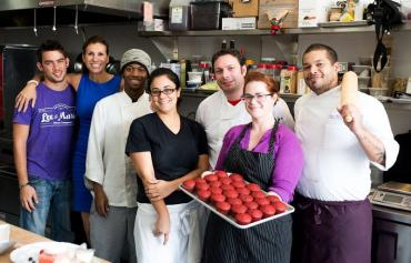 A group of adults working in a kitchen pose together